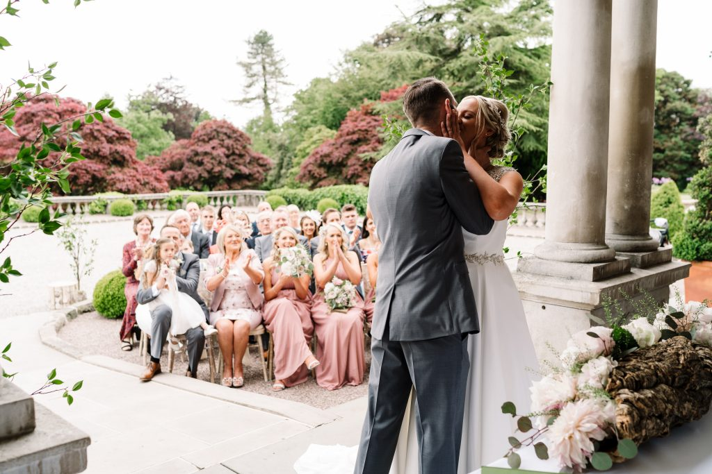 bride and groom kiss at the end of their Eaves Hall Outdoor Wedding ceremony