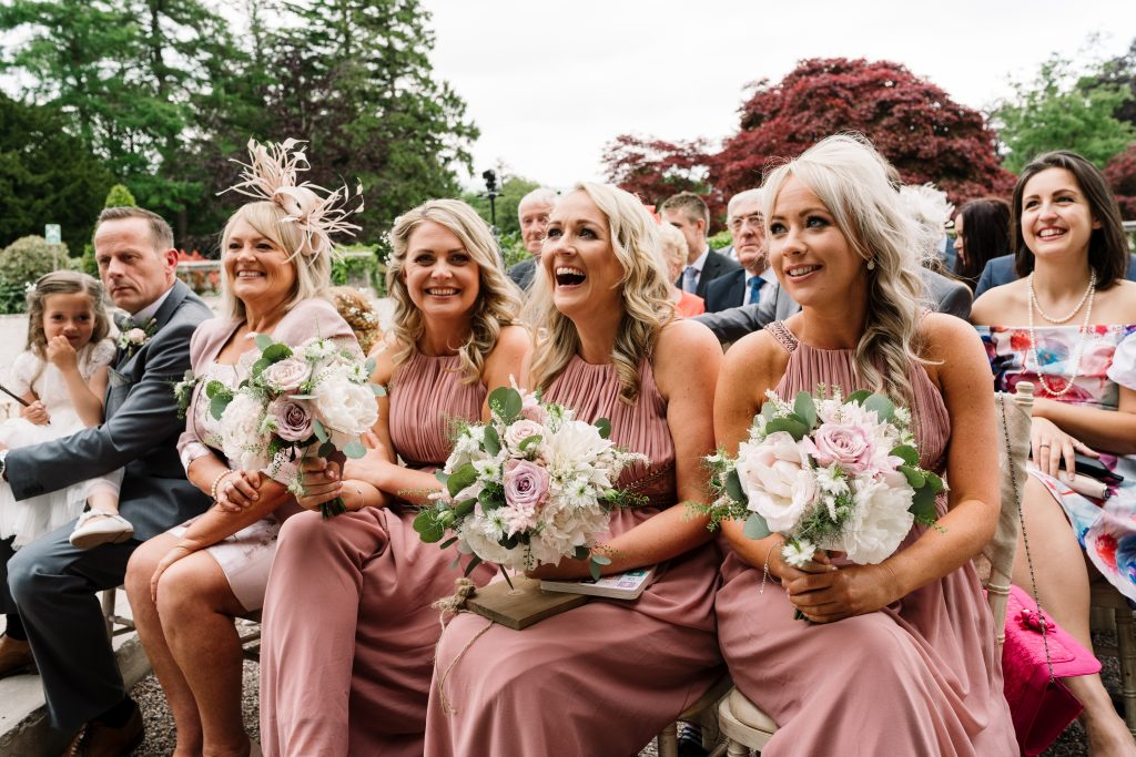 candid photo of bridesmaids laughing during the wedding ceremony