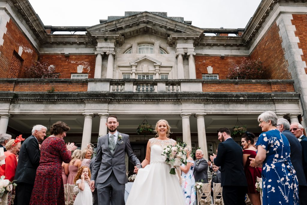 bride and groom walk back up the aisle together as husband and wife as guests clap