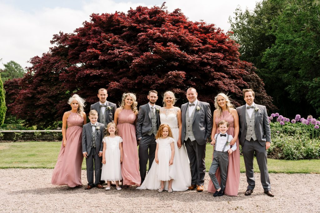 bridal party group photo with Eaves Hall gardens in the background