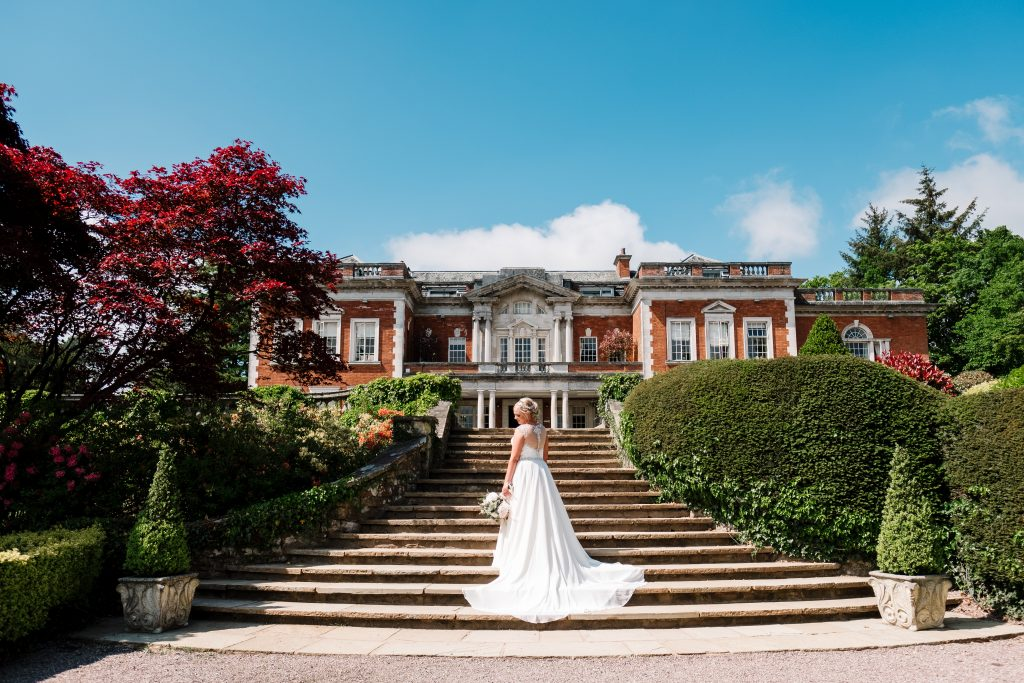 bride poses on the stairs in the gardens at Eaves Hall on a bright sunny day with blue skies