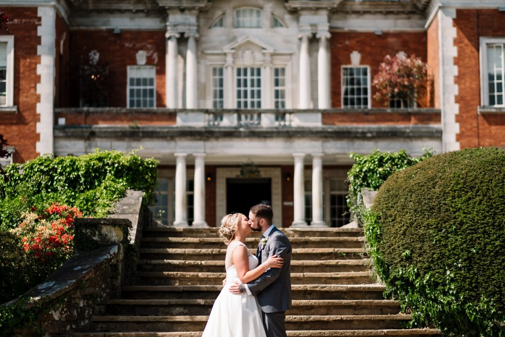 bride and groom kiss during a portrait at the couples Eaves Hall Outdoor Wedding