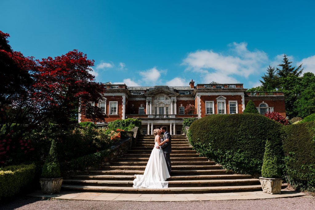 bride and groom portrait showing Eaves Hall in the background with brides dress flowing over the stairs
