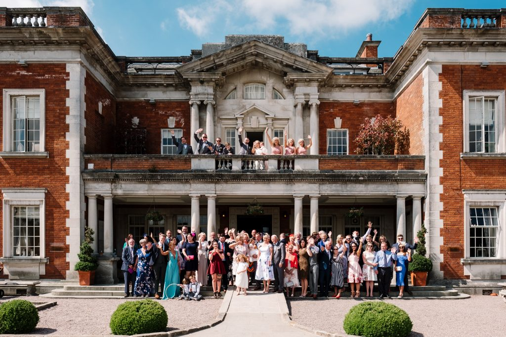 group photo of all guests attending the wedding outside Eaves Hall