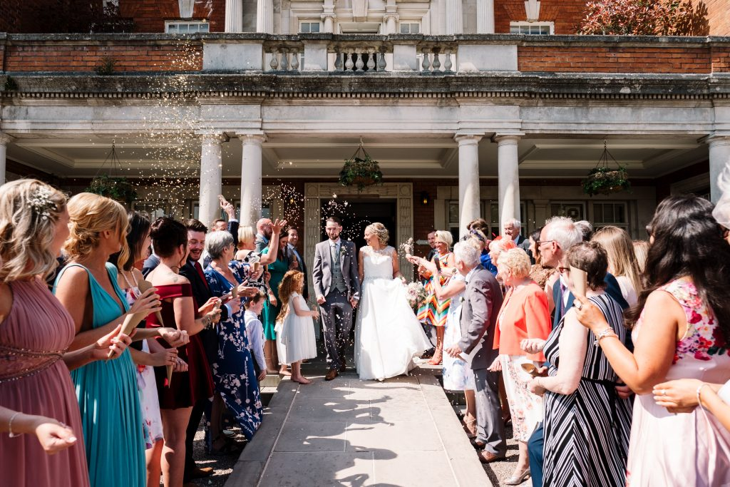 bride and groom walk out the front of Eaves Hall as guests throw confetti