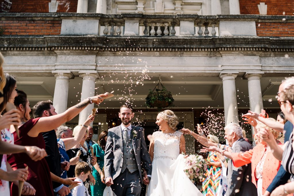 bride and groom hold hands as guests throw confetti to celebrate the wedding