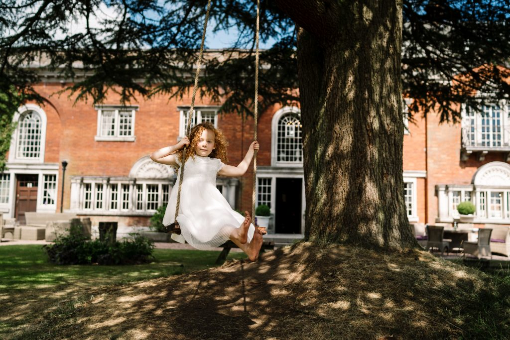 flower girl plays on a tree swing in the gardens at Eaves Hall