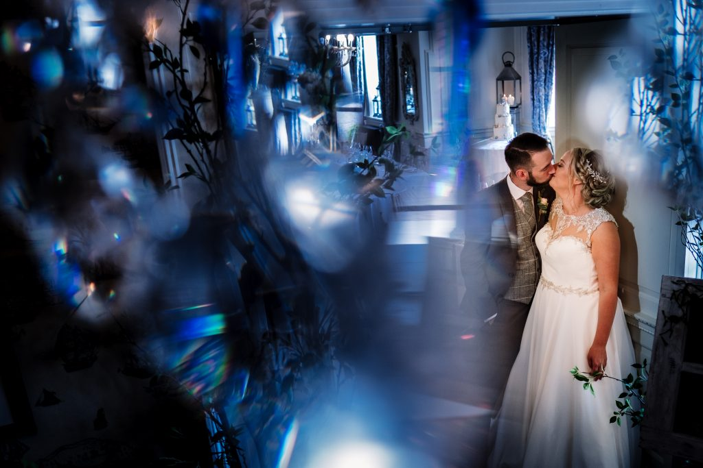bride and groom kiss during a couple portrait inside Eaves Hall