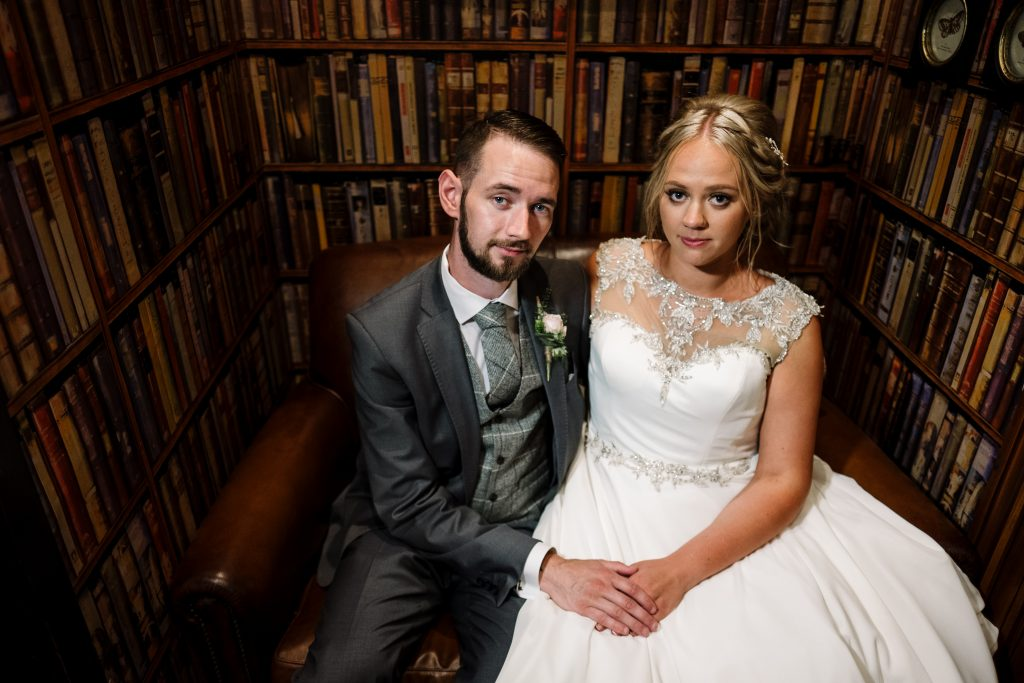 bride and groom sit in the library holding hands at Eaves Hall