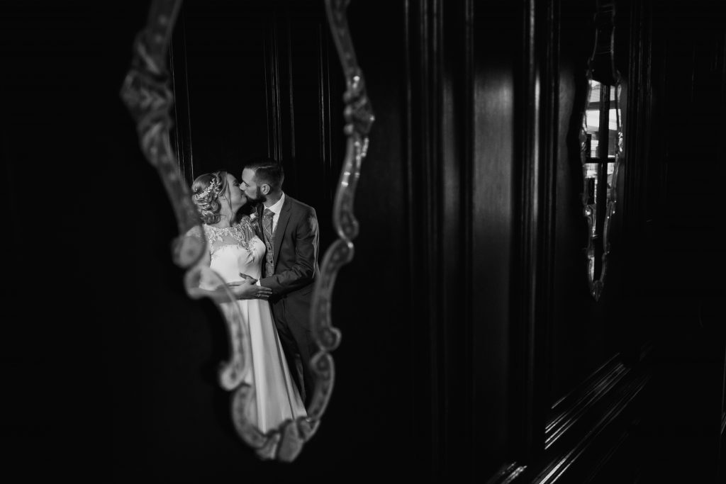 the mirror in the hallway of this Georgian mansion shows a reflection of bride and groom kissing