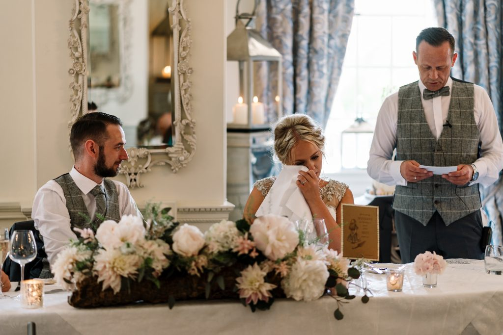 bride gets emotional during her fathers speech in the dining room at Eaves Hall