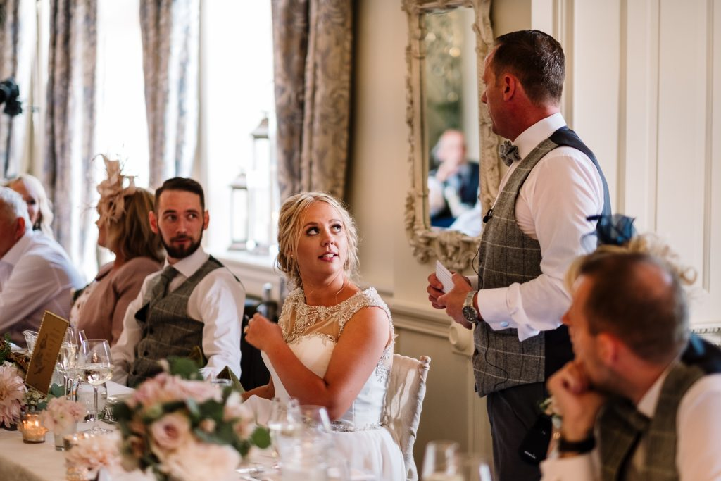 brides dad makes his speech in the Dining room as bride and groom look on