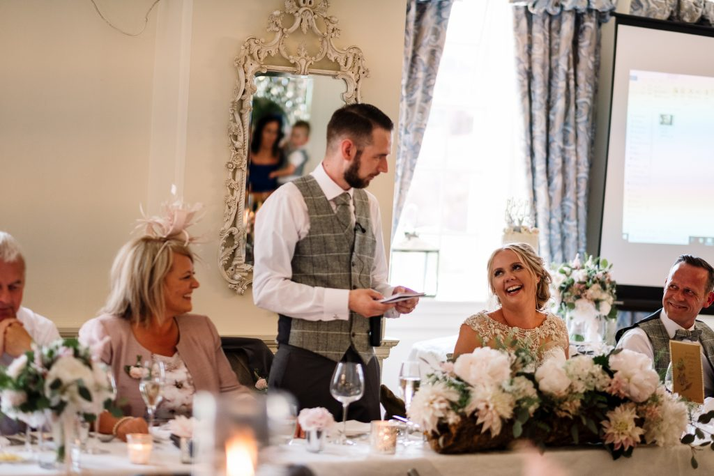 groom makes his speeches whilst bride laughs and guests watch