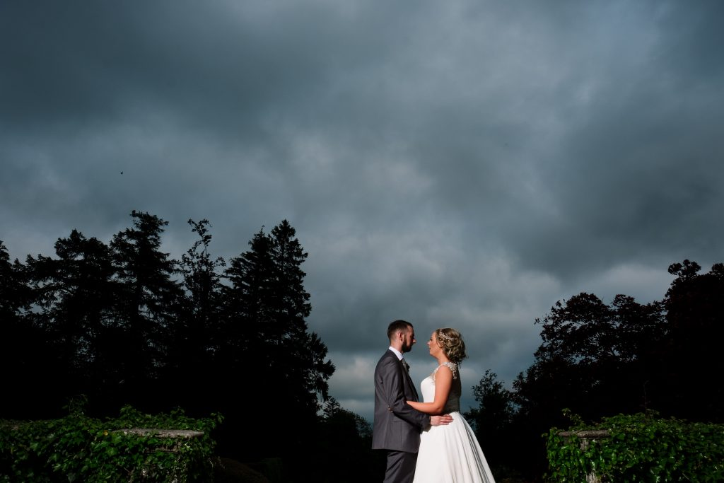 bride and groom portrait at dusk in the gardens at Eaves Hall wedding venue