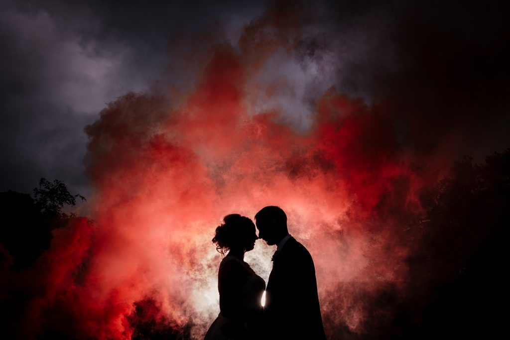 dramatic evening portrait with bride and groom featuring coloured smoke bombs
