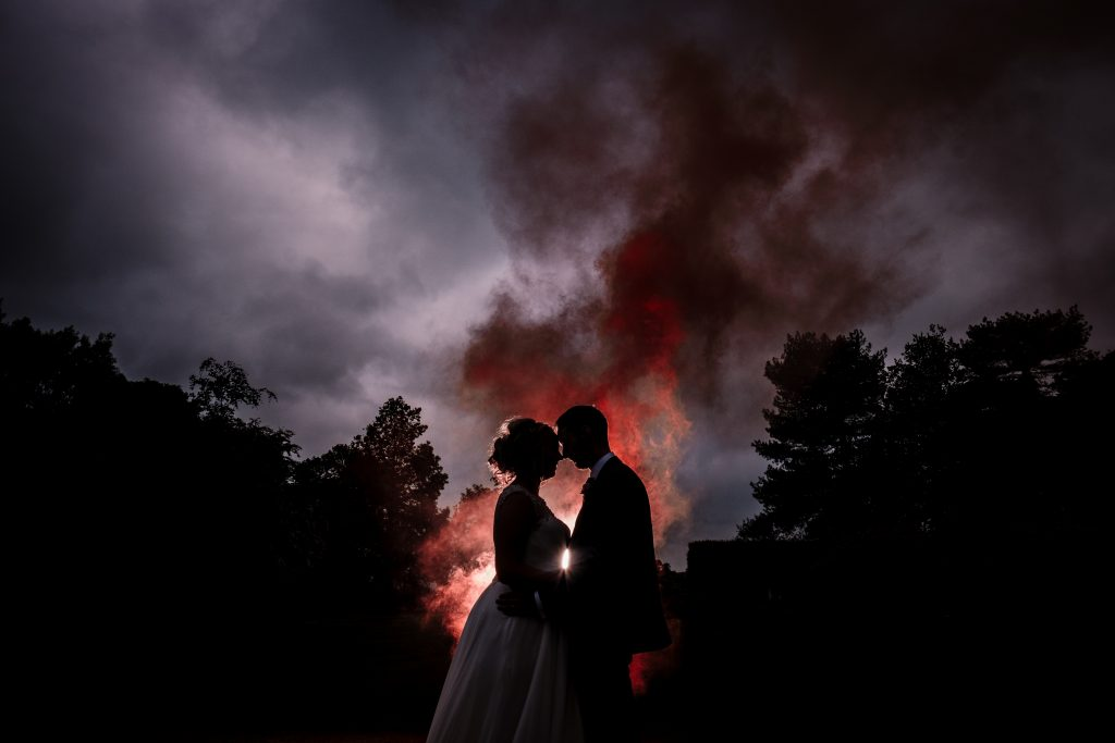 bride and groom portrait at night using red smoke bombs