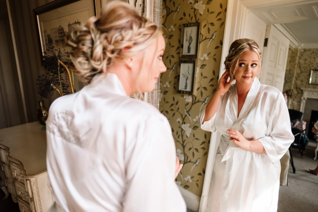 bride checks out her hair in the mirror in the bridal suite