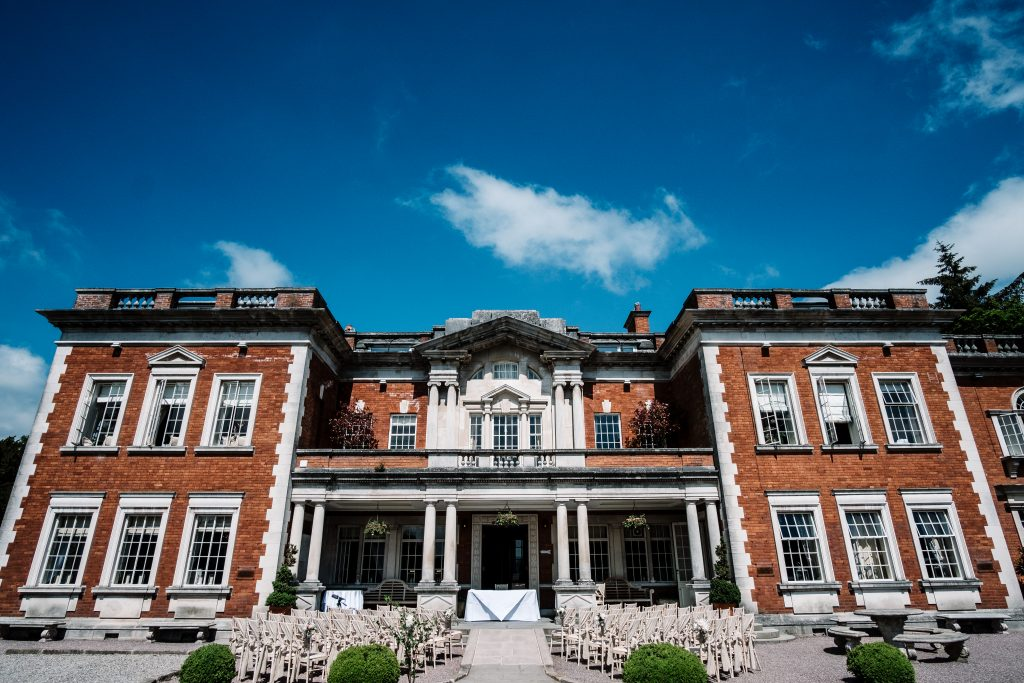 Eaves Hall on a sunny day with ceremony chairs outside ready for an outdoor wedding ceremony