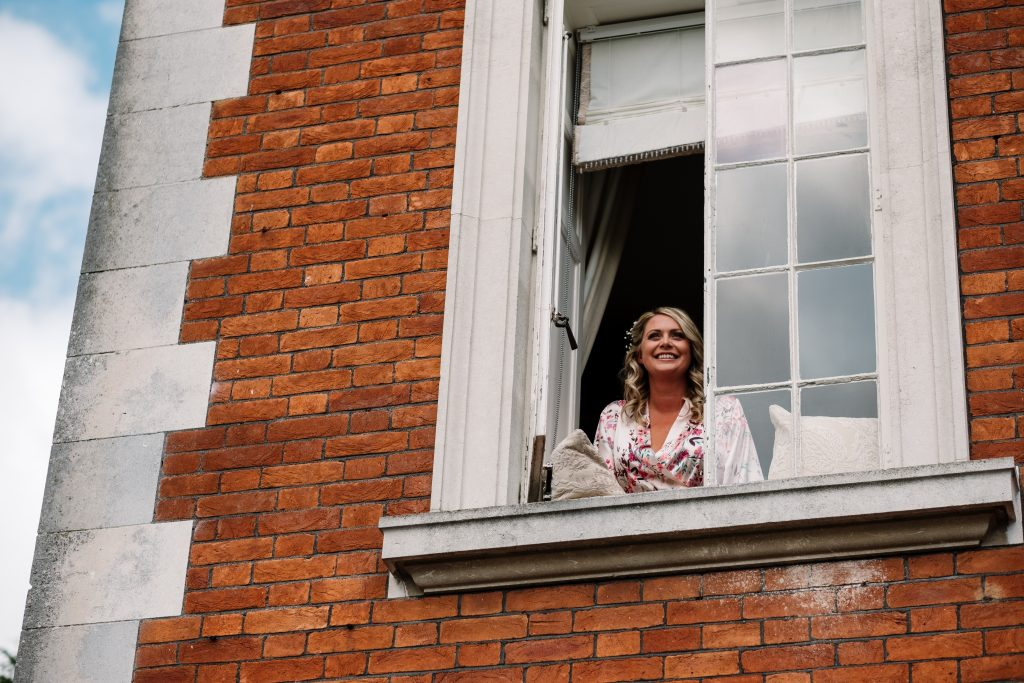 bride looks out of the window of the bridal suite of Eaves Hall, a Georgian mansion in the Ribble Valley