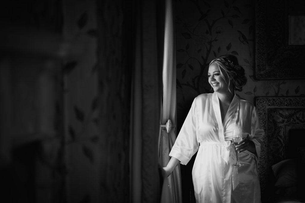 bride looks out of the window in the bridal suite at Eaves Hall