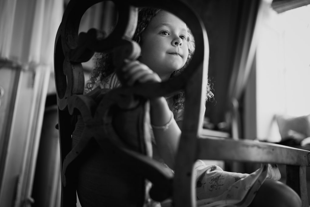 a flower girl sits in a chair and watches the bride and bridesmaids get ready for the wedding at Eaves Hall