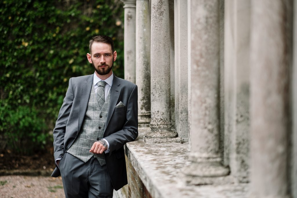 groom portrait featuring grey suite with grey checked waistcoat showing the pillar feature at the side of Eaves Hall.