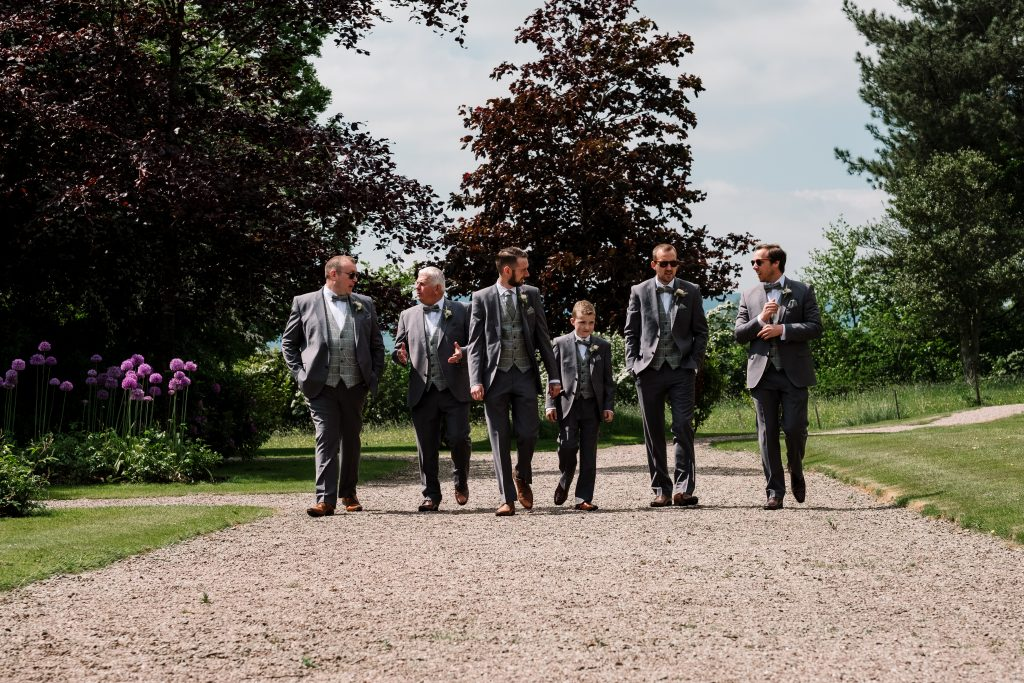 group photo featuring groom, best man and ushers walking in gardens at their Eaves Hall Wedding