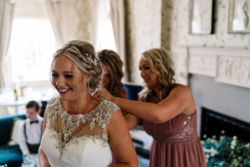 bridesmaids help the bride into her dress as the page boy waits patiently in the background