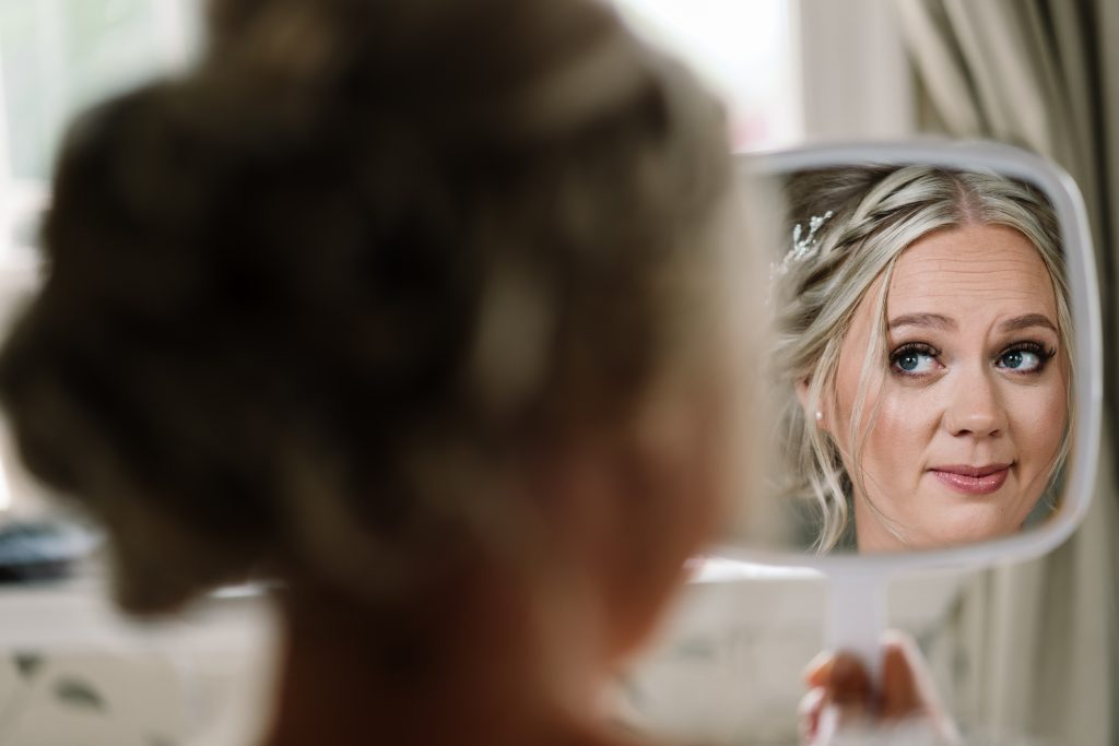 bride checks her make-up in the mirror