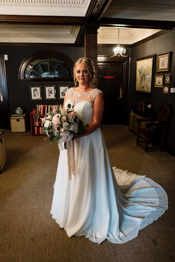 bride portrait featuring lace and sequin dress, holding a bouquet of white, ivory and pink flowers