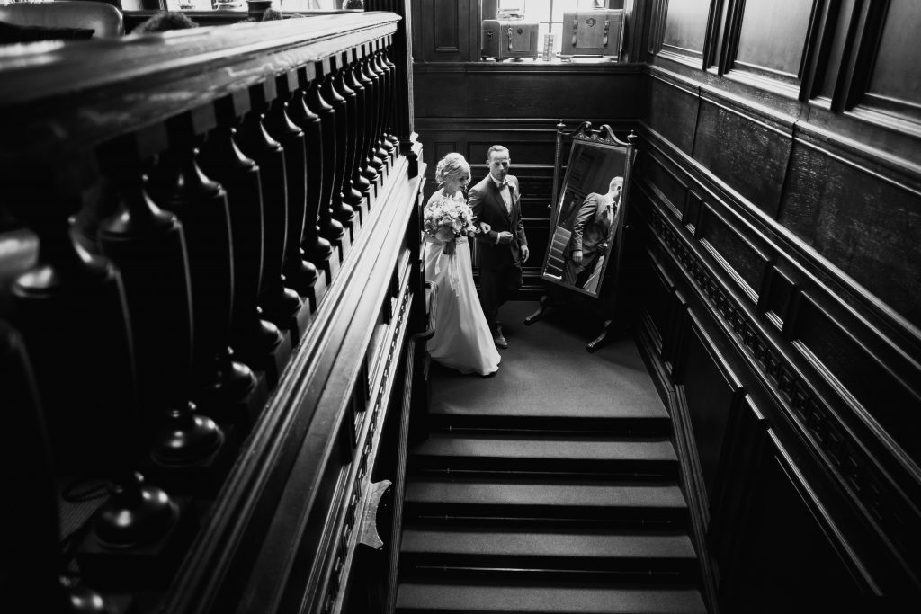 bride and dad walk down the stairs together heading for the wedding ceremony at Eaves Hall