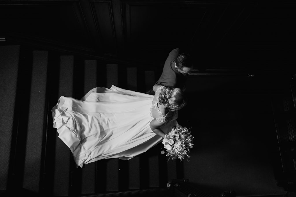 bride walks down the stairs at Eves Hall with her dad