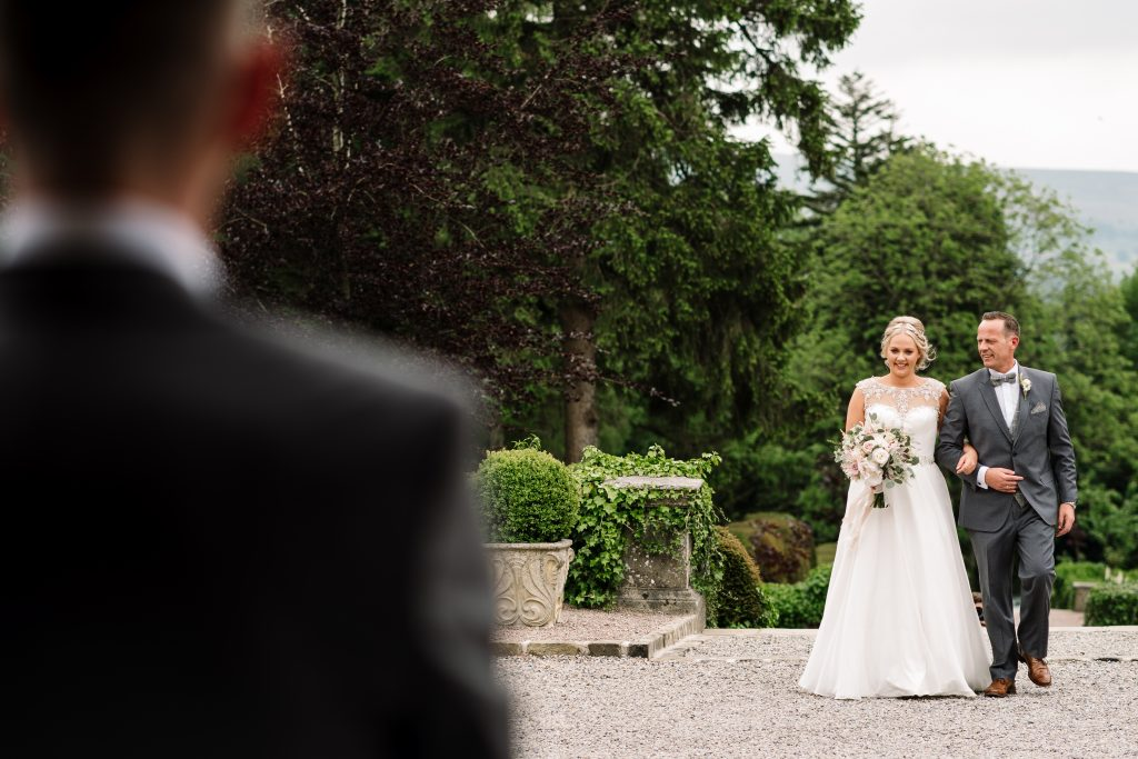 bride and dad walk hand in hand towards groom and their outdoor wedding ceremony