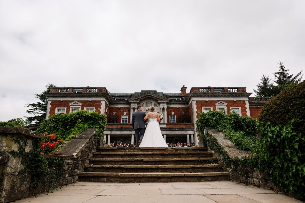 bride and her dad walk towards guests at her outdoor wedding ceremony at Eaves Hall