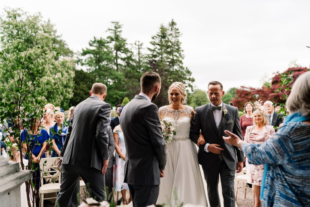 bride greets her groom as she walks down the aisle at her outdoor wedding