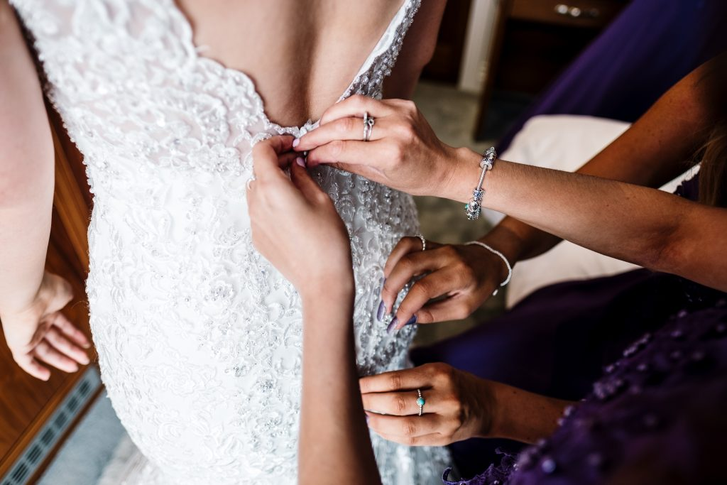 bride is fastened in to her dress during bridal preparations