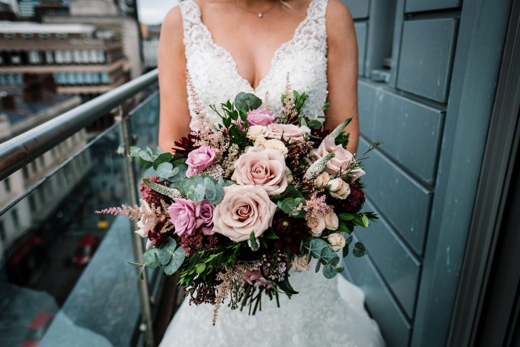 close-up of brides bouquet featuring pink, blush and burgundy flowers taken on the balcony outside the McCartney suite