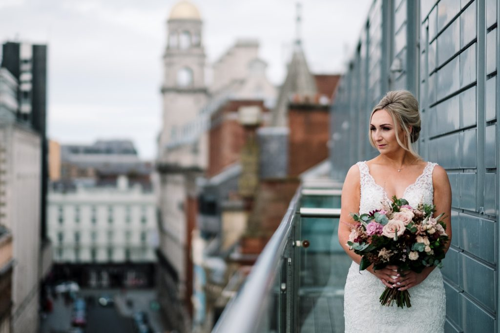 bride holds bouquet and looks at Liverpool city skyline from the McCartney suite balcony
