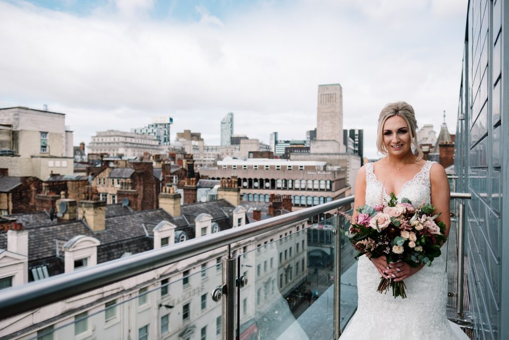 bride poses for a portrait with her bouquet with Liverpool skyline in the background