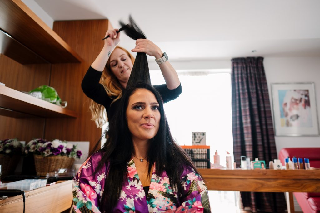 bridesmaid having her hair done during bridal preparations in the McCartney suite