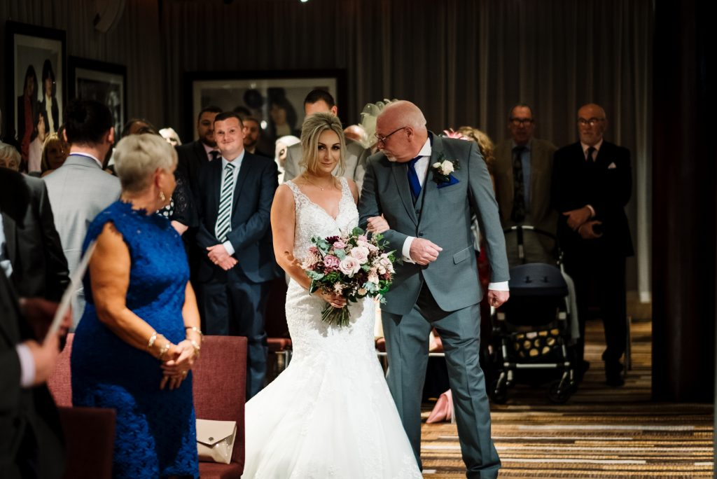 bride and her dad walk in to the room for her wedding ceremony as guests watch on