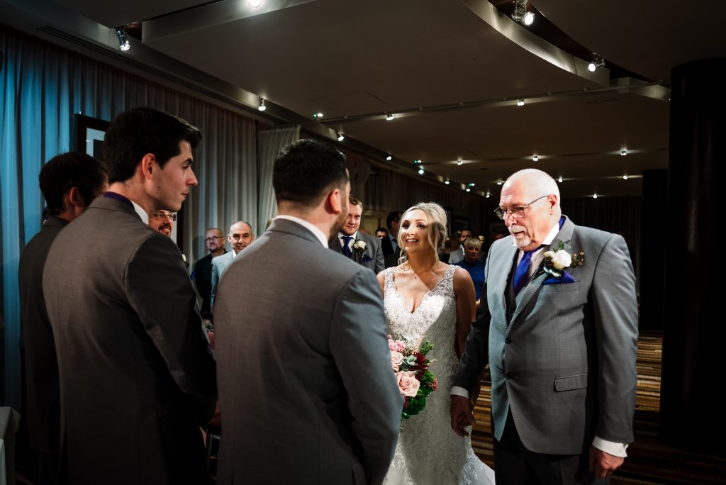 bride meets her groom at the bottom of the aisle in the Zygmant suite