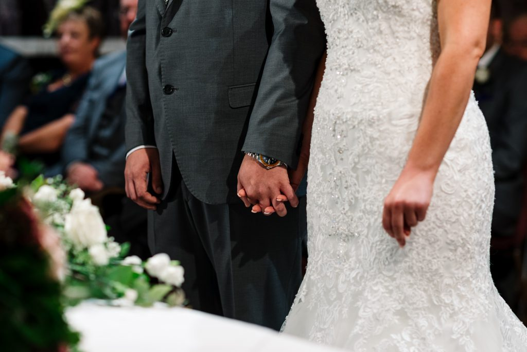 bride and groom hold hands during their wedding ceremony.