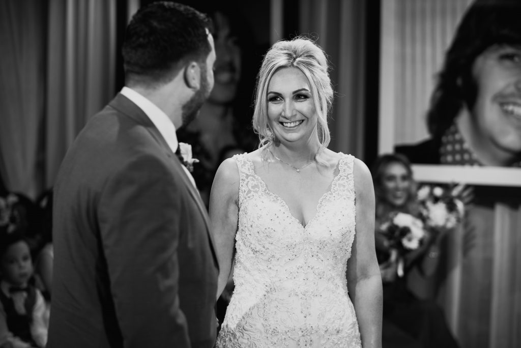 black and white photo of bride smiling at groom during their marriage ceremony