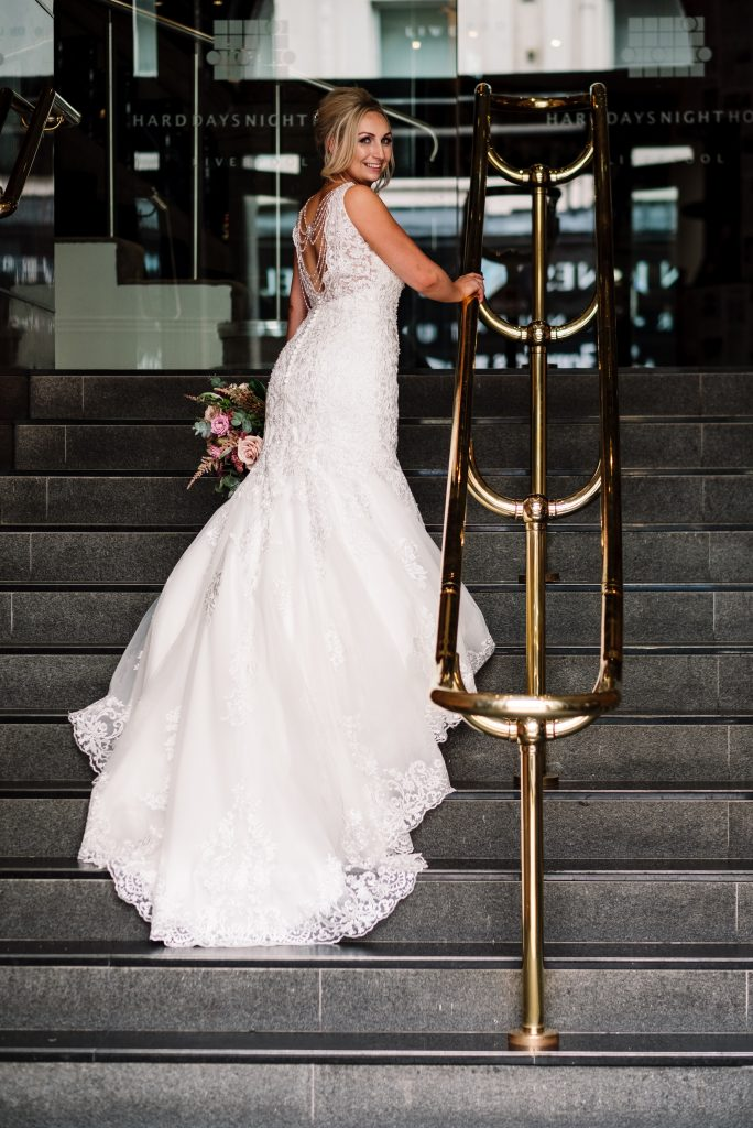 bride portrait with her dress cascading down the stairs at the Hard Day's Night hotel