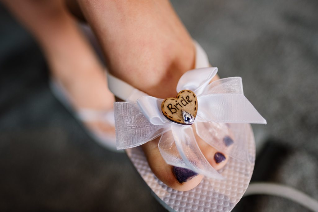 close-up photo of cute bride flip flops with 'bride' heart