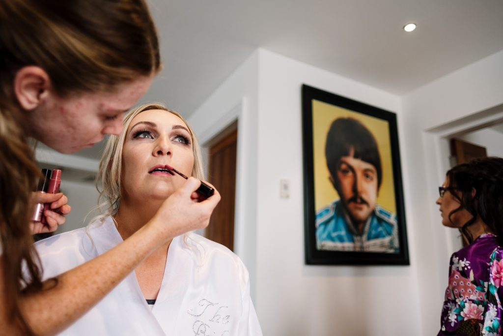 bride has lip gloss applied during wedding preparations