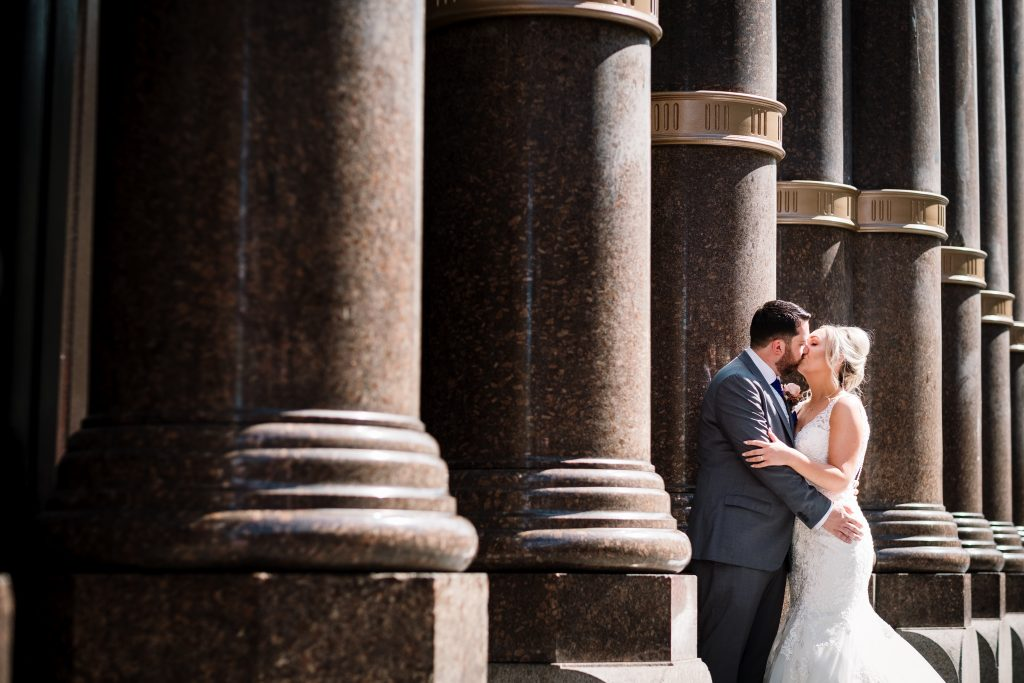 bride and groom kiss surrounded by marble pillars during their portraits outside the hard day's night hotel