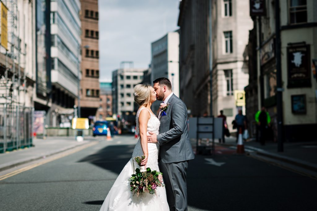 bride and groom kiss in the street during their Liverpool wedding day portrait shoot