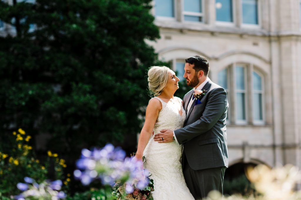 bride and groom pose for a portrait in St Nicks church gardens in Liverpool